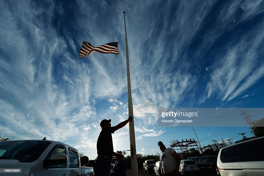 Bill Warren, a member of Veterans of Foreign Wars Post 4819, lowers the U.S. flag to half staff in memory of victims of the West Fertilizer Company explosion April 18, 2013 about 20 miles north of Waco in West, Texas. A fiery explosion that damaged or destroyed buildings within a half-mile radius ripped through the facility last night, injuring more than 160 people and killing an unknown number of others.