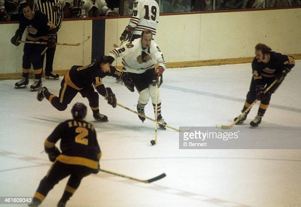 Bill White of the Chicago Blackhawks skates with the puck as he is defended by Butch Goring Terry Harper and Don Kozak of the Los Angeles Kings circa...