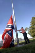 Bill Yates a security guard at Beauvoir Mansion the home where Jefferson Davis spent the last years of his life lowers the Confederate flag in...