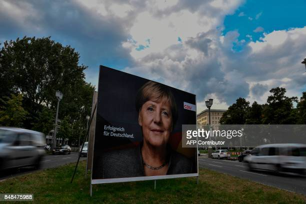TOPSHOT A billboard featuring German Chancellor and leader of the conservative Christian Democratic Union party Angela Merkel is pictured in Berlin...