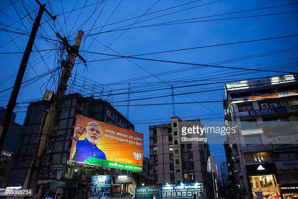A billboard for the Bharatiya Janta Party picturing Indian Prime Minister Narendra Modi is illuminated at night in Patna Bihar India on Friday July...