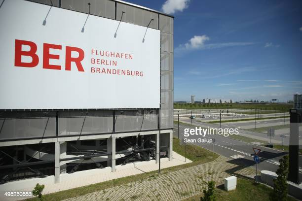 A billboard hangs on th side of a parking garage next to an empty parking lot at the unfinished new BER Willy Brandt Berlin Brandenburg International...