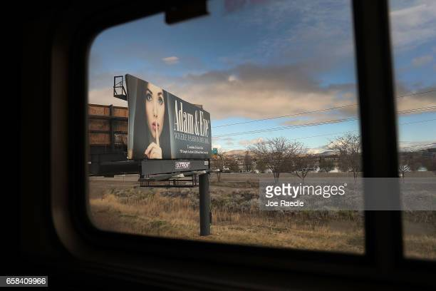 A billboard is seen as Amtrak's California Zephyr rolls through a town during its daily 2438mile trip to Emeryville/San Francisco from Chicago that...