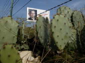 A billboard with the picture of US President George W Bush is posted behind barbed wire and cactus on the outskirts of Crawford Texas 03 August 2003...