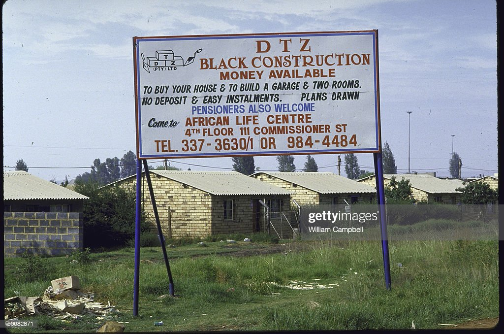 Billboards advertising good deals in building new homes in front of middleclass Black African houses re postpass law apartheid law limiting mobility...