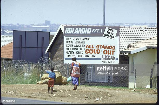 Billboards advertising good deals in building new homes re apartheid law limiting mobility of Blacks scrapped in 4/86