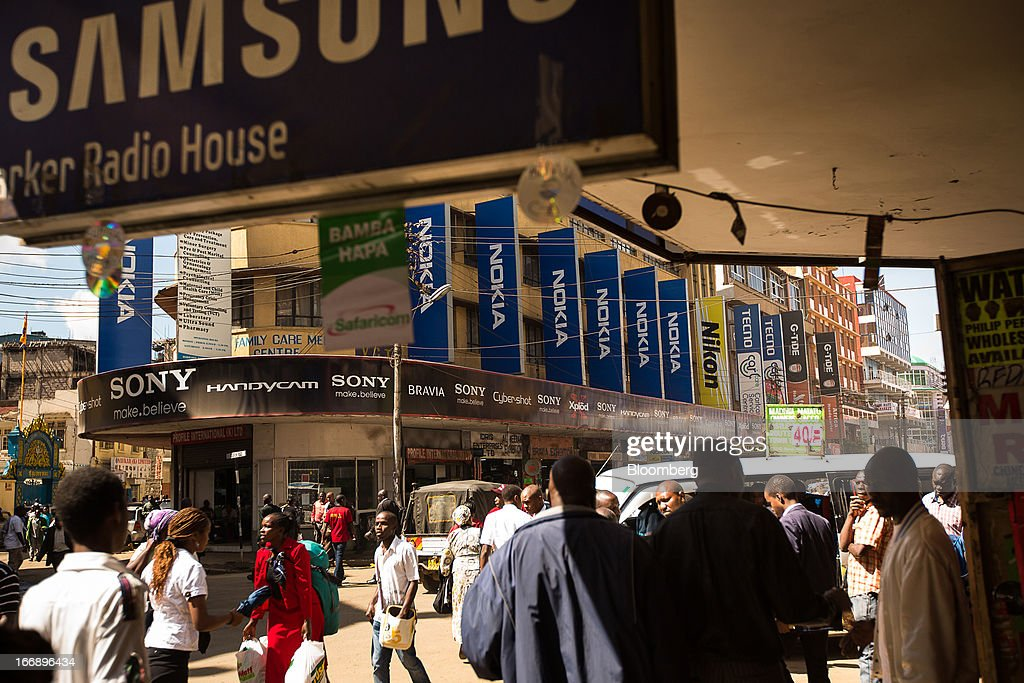 Billboards advertising Samsung Electronics Co. and Nokia Oyj mobile phones hang from buildings in Nairobi, Kenya, on Wednesday, April 17, 2013. Though only 23 percent of houses there have electricity and just 9 percent of roads are paved, mobile-phone penetration is 75 percent in the country, up from 5 percent in 2003. Photographer: Trevor Snapp/Bloomberg via Getty Images