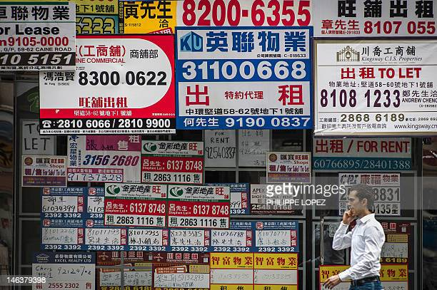 Billboards of real estate agents cover a wall in a street of Hong Kong on June 15 2012 As Hong Kong's new leadership is to take over in July with a...