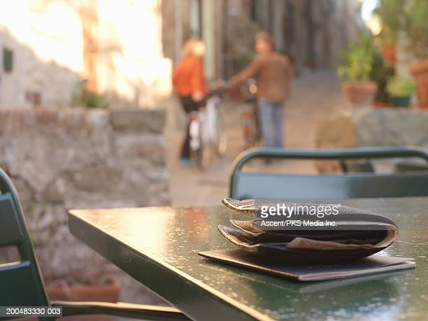 Billfold and passport on cafe table, couple walking away
