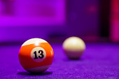 Billiard balls in a pool table. focus on the orange number 13 ball.