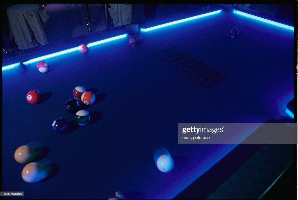 A billiards table at Bar Code has bright neon lights at its edges and the club's logo on the table Bar Code is a video arcade bar in Times Square...