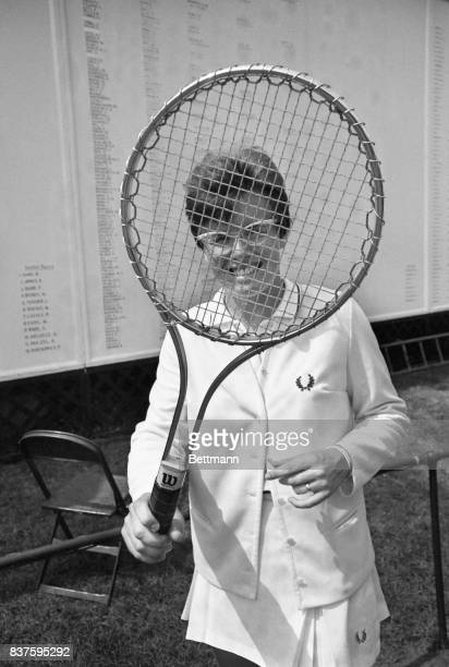 Billie Jean King winner of both the Wimbledon Crown and the US Lawn Tennis Championship smiles through the frame of the new steel tennis racket which...