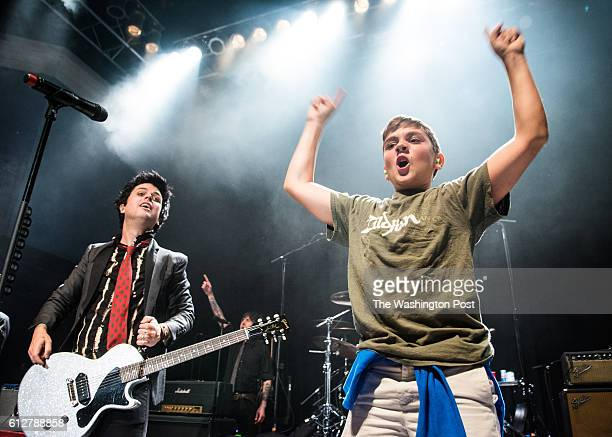 Billie Joe Armstrong of Green Day brings a young fan on stage to sing at their sold out show at the 930 Club on Monday