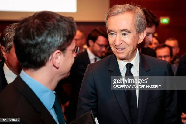 Group chief executive officer Bernard Arnault talks to a man after a press conference on April 25 2017 in Paris LVMH which already owns Christian...