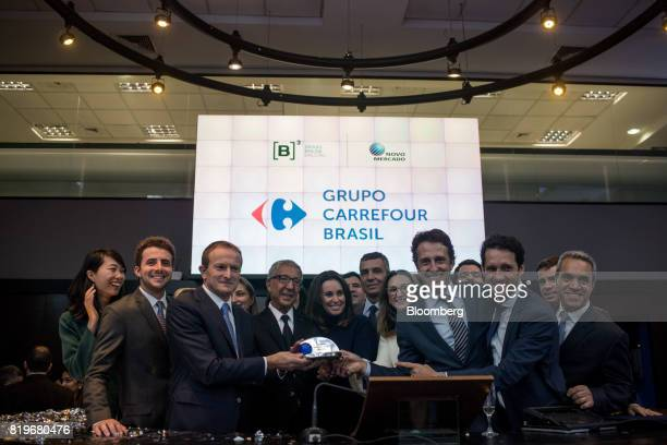 Billionaire Abilio Diniz fourth left and Charles Desmartis chief executive officer of Grupo Carrefour Brasil third left ring the opening bell during...