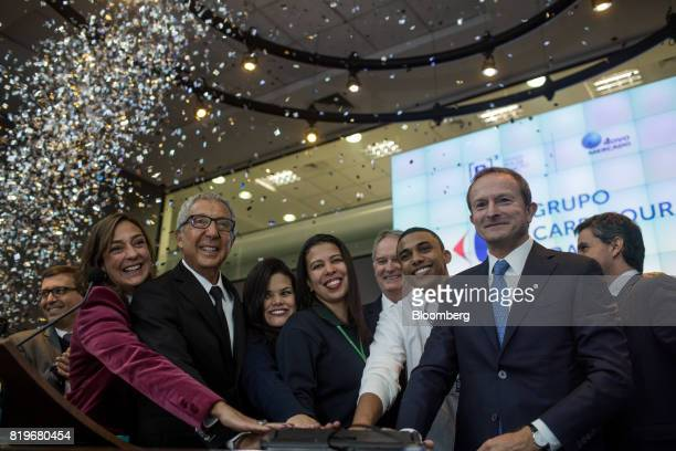 Billionaire Abilio Diniz second left and Charles Desmartis chief executive officer of Grupo Carrefour Brasil right ring the opening bell during the...