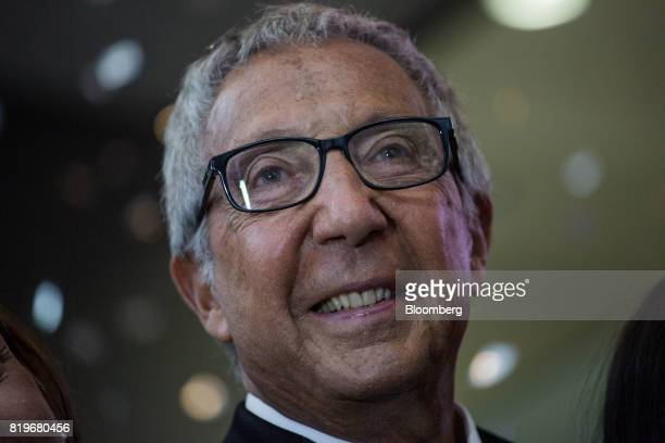 Billionaire Abilio Diniz smiles while ringing the opening bell during the initial public offering of Atacadao SA the Brazilian unit of French...