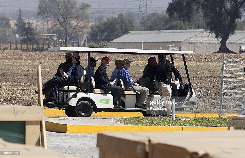 Billionaire Bill Gates, center, with blue shirt, rides in a golf cart during a tour of the research facility of the International Maize and Wheat Improvement Center, known by its Spanish initials as CIMMYT, in Texcoco, Mexico, on Wednesday, Feb. 13, 2013. The group, which performs research for agricultural productivity, opens its research facility this week. Photographer: Susana Gonzalez/Bloomberg via Getty Images
