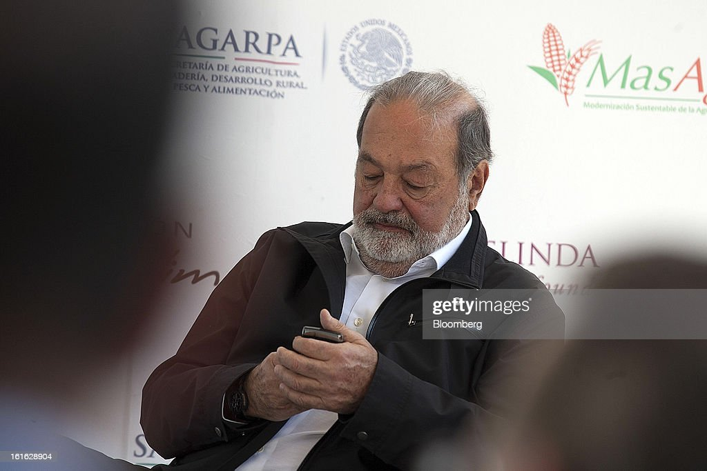 Billionaire Carlos Slim checks his mobile device during a news conference with Bill Gates, unseen, to announce donations to Mexico's International Maize and Wheat Improvement Center, known by its Spanish initials as CIMMYT, in Texcoco, Mexico, on Wednesday, Feb. 13, 2013. The group, which performs research for agricultural productivity, will open its research facility this week. Photographer: Susana Gonzalez/Bloomberg via Getty Images