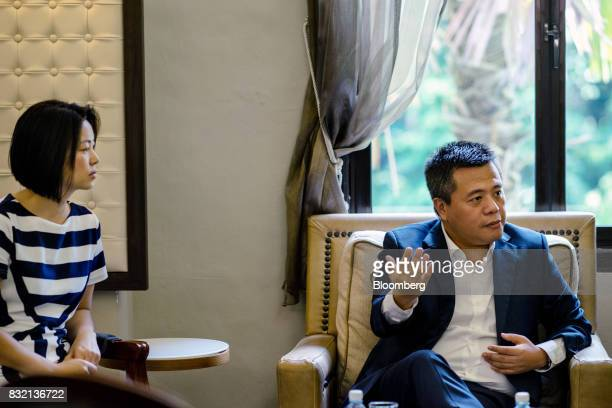 Billionaire Chen Tianqiao founder and chairman of Shanda Group right speaks as his wife Chrissy Luo cofounder and vice chairman looks on during an...