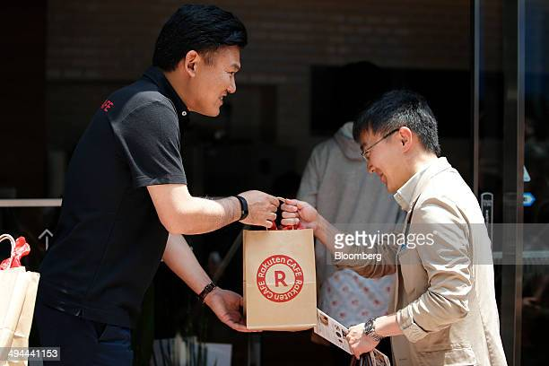 Billionaire Hiroshi Mikitani chairman and chief executive officer of Rakuten Inc left presents a customer with a gift bag during the opening ceremony...