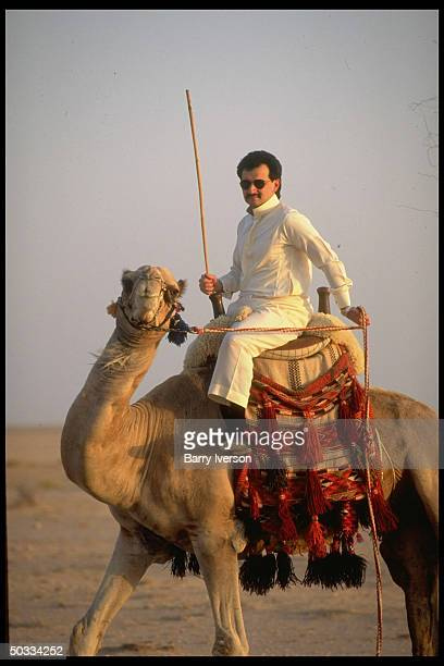 Billionaire investor Saudi Prince Alwaleed astride camel at his weekend desert retreat 45 miles from Riyadh