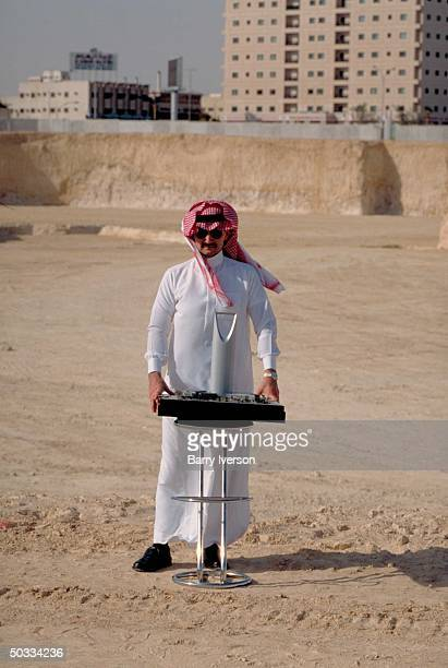 Billionaire investor Saudi Prince Alwaleed poised in lot w model of prob of 1 of his Kingdom Holding Co bldg projects