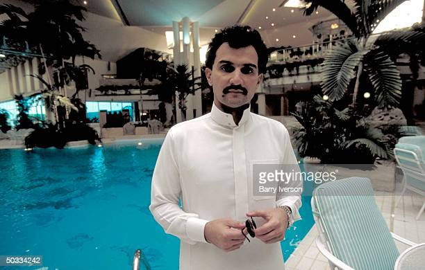 Billionaire investor Saudi Prince Alwaleed poised overlooking his elaborately landscaped palace swimming pool