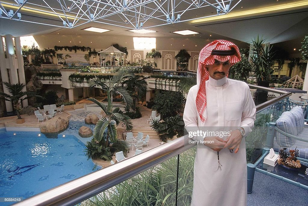Billionaire investor Saudi Prince Alwaleed poised overlooking his elaborately landscaped palace swimming pool.