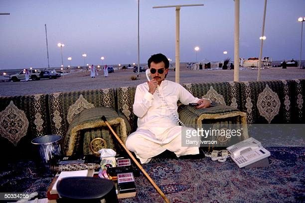 Billionaire investor Saudi Prince Alwaleed taking phone call while relaxing by sunset at his weekend desert retreat 45 miles from Riyadh
