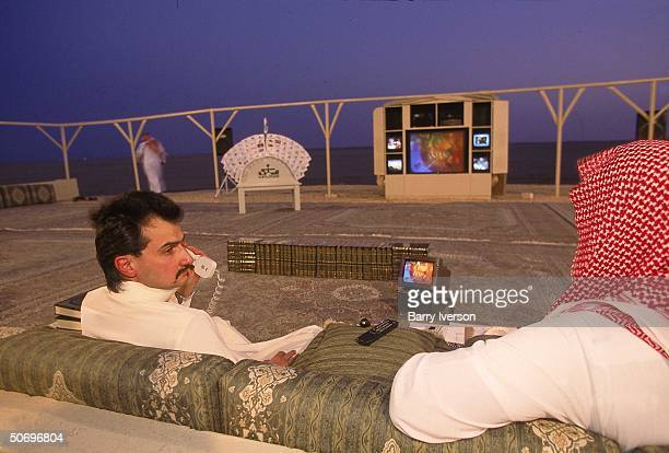 Billionaire investor Saudi Prince Alwaleed watching CNN broadcast on Asian enonomy on hightech TV console set up outside at his weekend desert...