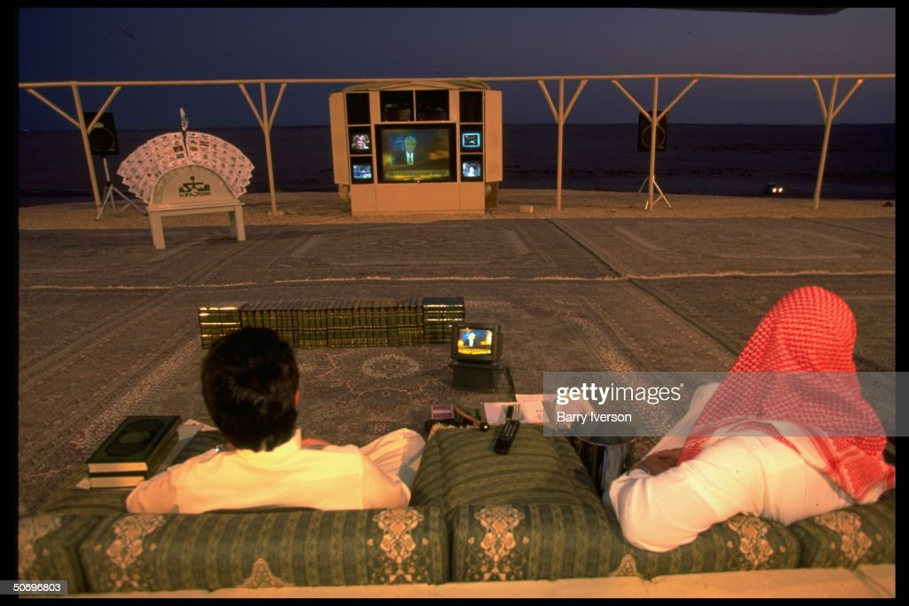 Billionaire investor Saudi Prince Alwaleed (L) watching CNN's Lou Dobbs on Moneyline on high-tech TV console set up outside at his weekend desert retreat 45 miles from Riyadh.