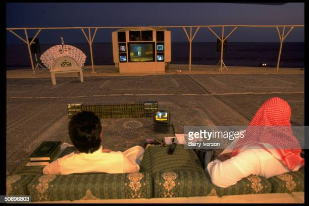 Billionaire investor Saudi Prince Alwaleed watching CNN's Lou Dobbs on Moneyline on hightech TV console set up outside at his weekend desert retreat...