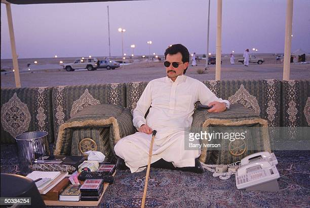 Billionaire investor Saudi Prince Alwaleed watching TV remote control inhand by sunset at his weekend desert retreat 45 miles from Riyadh