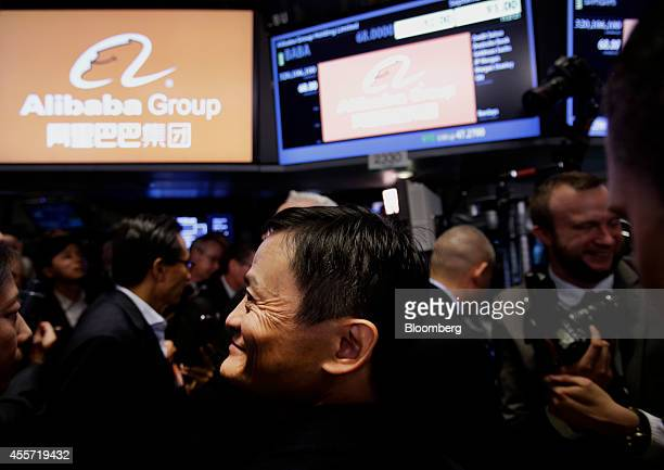 Billionaire Jack Ma chairman of Alibaba Group Holding Ltd center smiles while touring the floor of the New York Stock Exchange in New York US on...