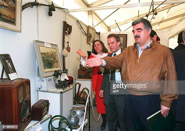 Billionaire Lebanese Prime Minister Rafic Hariri points at an old radio set during a tour of the first Lebanese postwar flea market 03 March in...