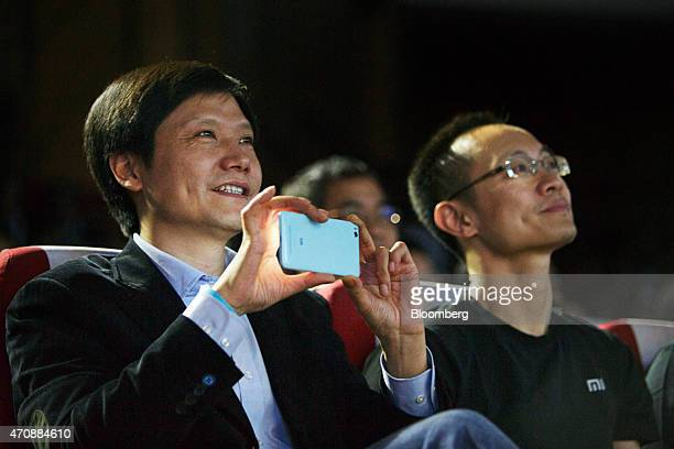 Billionaire Lei Jun chairman and chief executive officer of Xiaomi Corp left holds a smartphone as Bin Lin president and cofounder looks on during a...