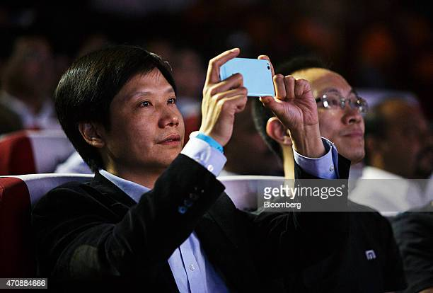 Billionaire Lei Jun chairman and chief executive officer of Xiaomi Corp left takes a photograph with a smartphone as Bin Lin president and cofounder...