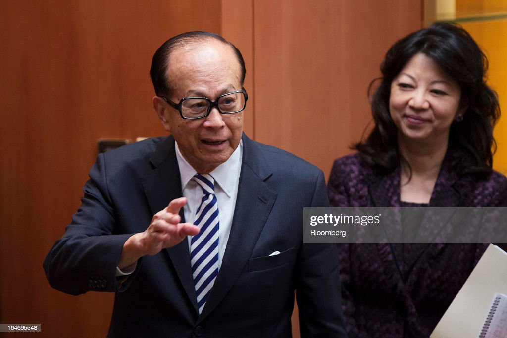 Billionaire Li Ka-shing, chairman of Cheung Kong (Holdings) Ltd. and Hutchison Whampoa Ltd., left, gestures to reporters after a news conference in Hong Kong, China, on Tuesday, March 26, 2013. Cheung Kong Holdings, the builder controlled by Asia's richest man, said 2012 profit excluding contributions from unit Hutchison Whampoa Ltd. rose 6 percent as rental income growth offset a decline in home sales. Photographer: Jerome Favre/Bloomberg via Getty Images