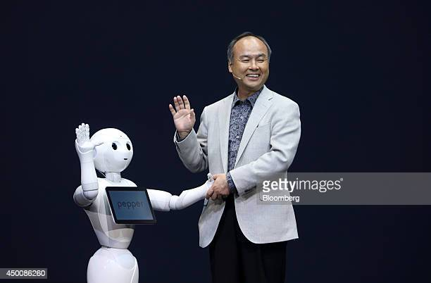 Billionaire Masayoshi Son chairman and chief executive officer of SoftBank Corp shakes hands with a humanlike robot called Pepper developed by the...