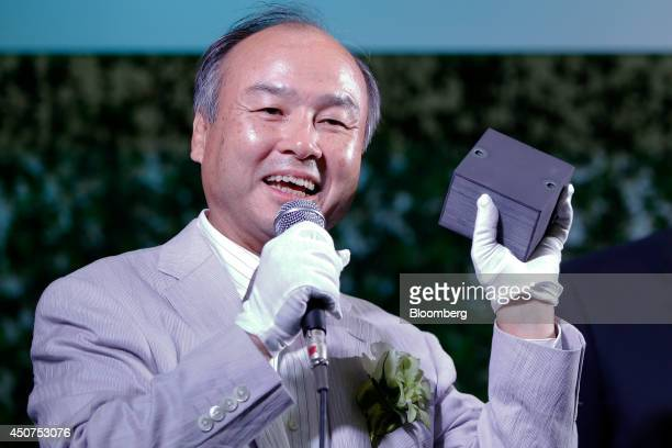 Billionaire Masayoshi Son chairman and chief executive officer of SoftBank Corp holds a stack of fuel cells for Bloom Energy Corp's Bloom Energy...