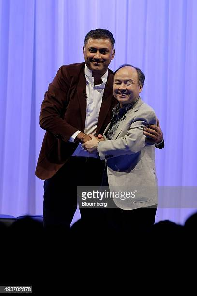 Billionaire Masayoshi Son chairman and chief executive officer of SoftBank Group Corp right shakes hands with Nikesh Arora president and chief...