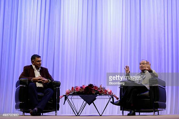 Billionaire Masayoshi Son chairman and chief executive officer of SoftBank Group Corp right gestures as he speaks with Nikesh Arora president and...