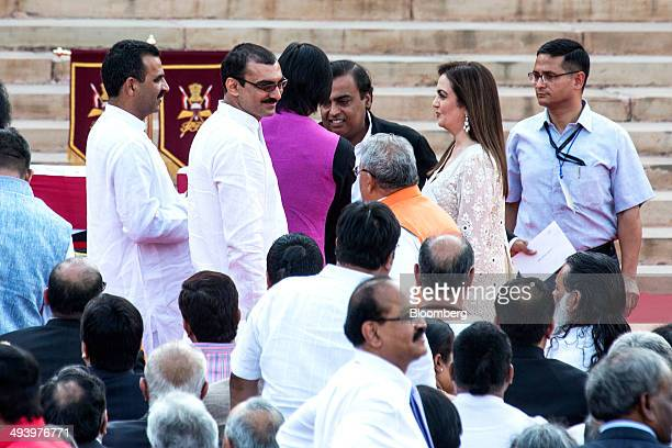 Billionaire Mukesh Ambani chairman of Reliance Industries Ltd top third from right and his wife Nita Ambani top second from right attend the swearing...