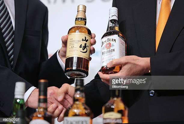 Billionaire Nobutada Saji chairman and chief executive officer of Suntory Holdings Ltd right shakes hands with Matt Shattock chief executive officer...