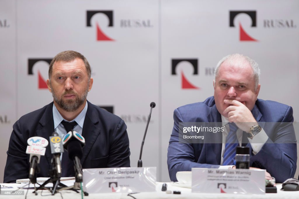 Billionaire Oleg Deripaska chief executive officer of United Co Rusal left and Matthias Warnig chairman listen during a press conference in Hong Kong...