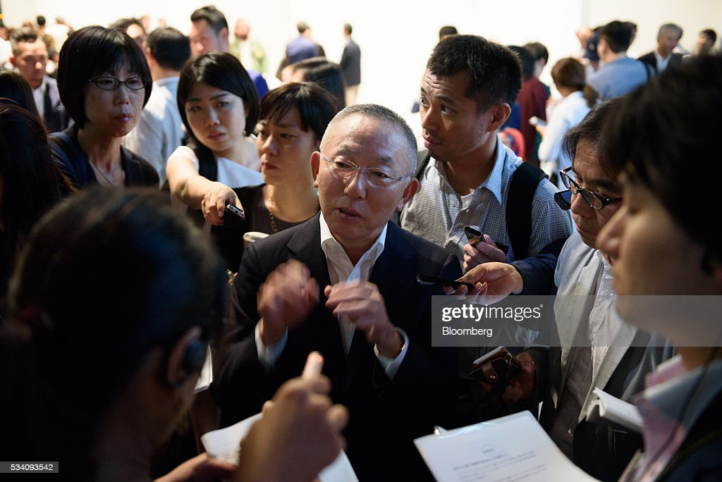 Billionaire Tadashi Yanai, chairman and chief executive officer of Fast Retailing Co., center, speaks to members of the media during a preview of the Uniqlo 2016 Fall-Winter lineup in Tokyo, Japan, on Wednesday, May 25, 2016. Analysts and investors will be watching as Uniqlo unveils the new season's LifeWear line in Tokyo to see whether Yanai will come through with his pledge to offer the 'lowest possible prices.' Photographer: Akio Kon/Bloomberg via Getty Images