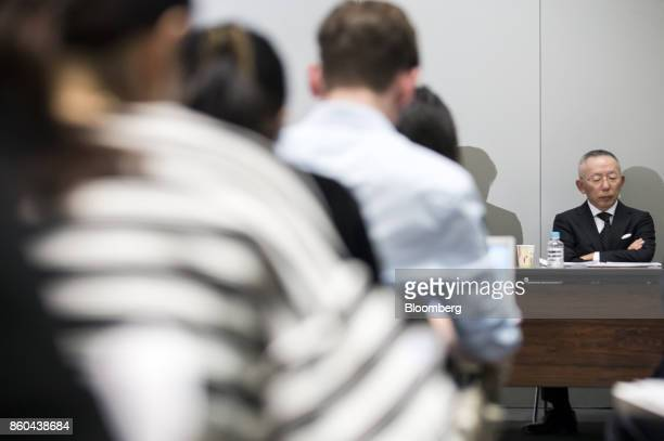 Billionaire Tadashi Yanai chairman and chief executive officer of Fast Retailing Co right listens during a news conference at the Tokyo Stock...