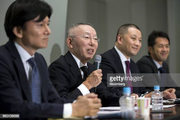 Billionaire Tadashi Yanai chairman and chief executive officer of Fast Retailing Co second left speaks during a news conference at the Tokyo Stock...