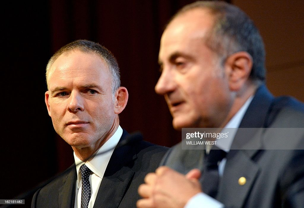 BHP Billiton CEO Marius Kloppers (L) listens as company chairman Jac Nasser (R) announces Kloppers is retiring and will be replaced by Andrew Mackenzie, in Sydney on February 20, 2013. The 56-year-old Mackenzie, currently chief executive non-ferrous, has over 30 years experience in oil and gas, petrochemicals and minerals and joined BHP Billiton in November 2008. South African Kloppers has been running the world's largest miner since October 2007, steering it through the global financial crisis. AFP PHOTO/William WEST